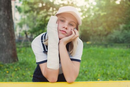 Boring teenage girl young sportswoman with arm injury outdoors