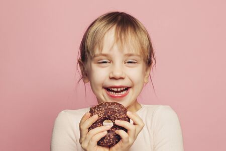 Cute little girl laughing and having fun with chocolate donut on pink color background 版權商用圖片