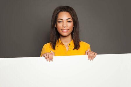 Happy african american woman holding white empty signboard 版權商用圖片