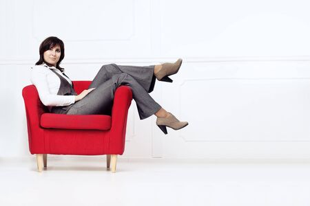 Director rests after hard work. Stylish Woman in a Red Armchair.