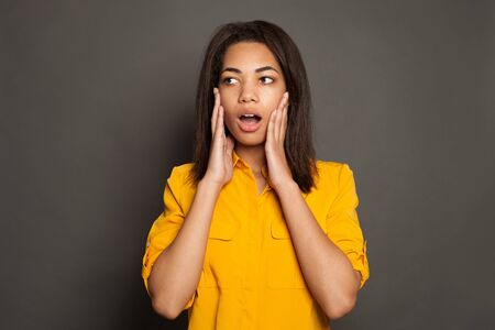 Shocked surprised black woman in yellow shirt on gray studio background