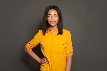 Portrait of happy successful black young woman in yellow shirt on gray studio background 版權商用圖片