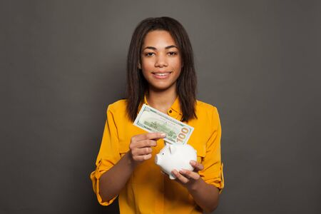 Happy confident black woman putting in money box 100 dollars banknote