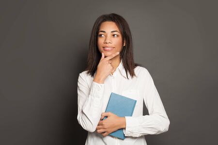 Studio portrait of positive thinking mixed race ethnicity young black woman in white shirt with book on gray  background 版權商用圖片