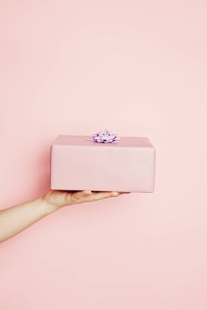 Beautiful minimal background with pink gift box in female hand on pink background