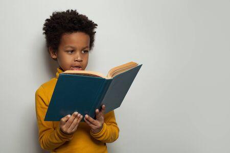 Portrait of little black child boy reading a book on white background 版權商用圖片