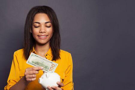 Pretty black girl putting in money box 100 dollars banknote