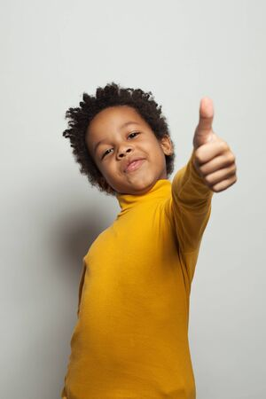 Small black kid boy holding thumb up and smiling on white background 版權商用圖片