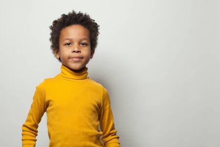 Portrait of smart little black kid boy on white background