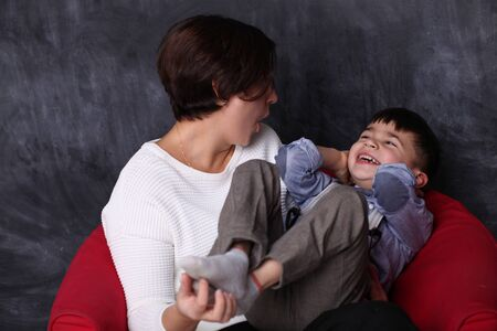 Mother is playing with her son. Mom tickles the boy and laughs with him