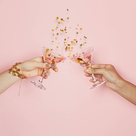 Celebration and holiday background. Two hands holding wine glasses with gold confetti on pink background Banco de Imagens