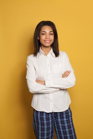 Happy young black woman with crossed arms standing against bright yellow background 版權商用圖片