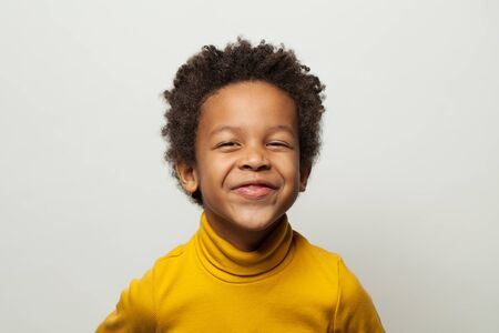 Funny happy little black kid boy laughing on white background