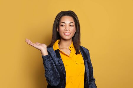 Young black woman with empty open hand for advertising marketing or product placement standing on colorful yellow background 版權商用圖片