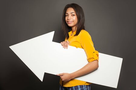 Happy african american woman holding white empty growing arrow signboard