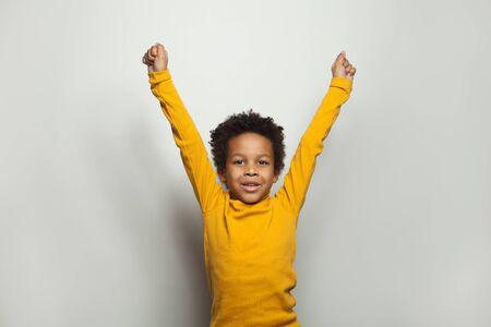 Little black kid boy having fun on white background