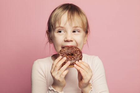 Cute little girl holding chocolate donut. Happy Child on pink background