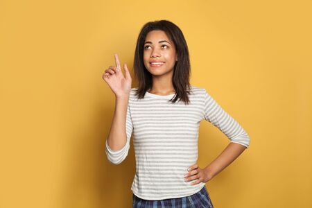 Pretty african american woman pointing finger up on bright yellow studio background