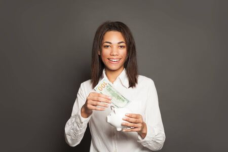 Smart successful african american woman putting in piggy bank one hundred dollars banknote 版權商用圖片