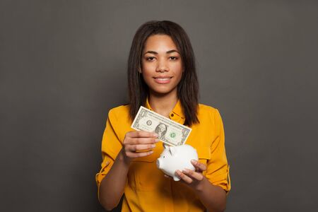 Smart black woman putting in piggy bank one dollars banknote