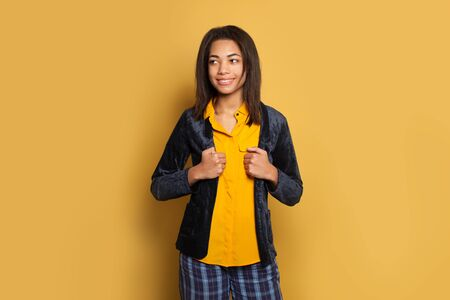 Attractive African American woman smiling against bright yellow wall background 版權商用圖片