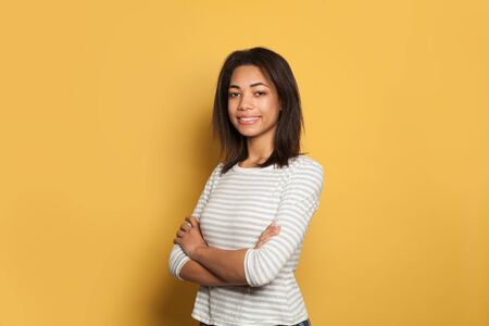 Cheerful black woman in white shirt on colorful yellow background 版權商用圖片