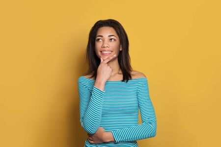 Pretty black woman in blue shirt thinking and looking up aside on colorful yellow background