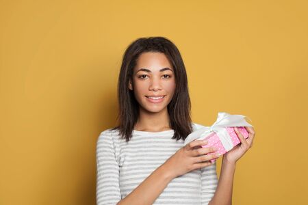 Smiling black woman with gift on colorful yellow background
