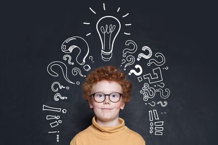 Redhead kid with lightbulb and question marks on blackboard background. Brainstorming and idea concept 版權商用圖片