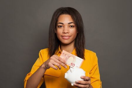 Young smart black woman putting in piggy bank euro banknote