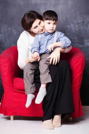 mom and her son are sitting in a red chair