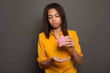 Unhappy black woman and empty piggy bank
