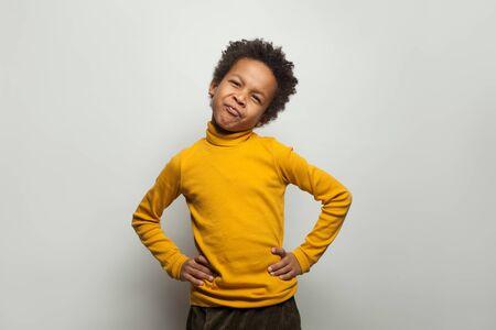 Small black child boy grimacing on white background