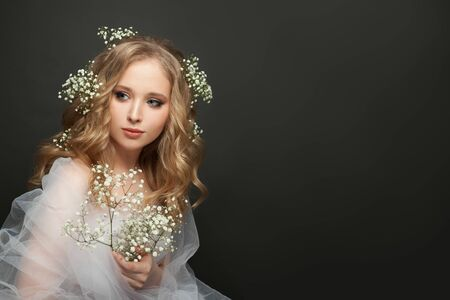 Beautiful bride woman with blonde curly hairdo wearing white tulle dress