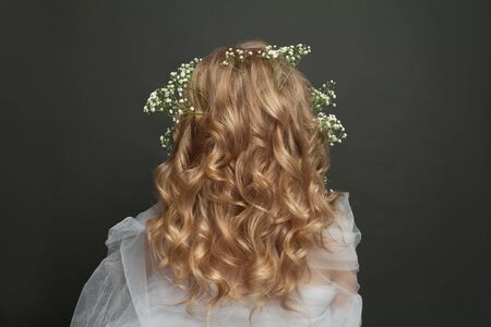 Beautiful female back with long blonde curly hair. Perfect wedding hairdo Stock Photo