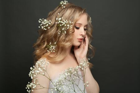 Young woman with flowers portrait on black background