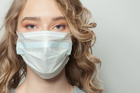 Portrait of woman in a face mask on white background