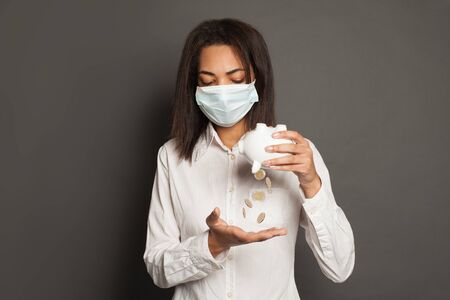 Financial crisis and pandemic concept. Young black woman in medical mack without money