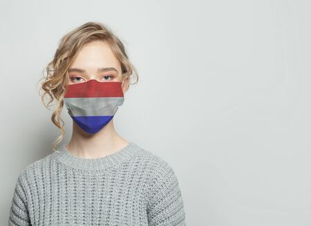 Young woman wearing a face mask with flag. Flu epidemic and virus protection concept
