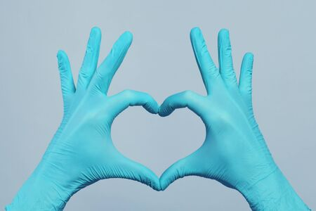 Hands in blue doctor gloves making heart on gray background. Medical assistance concept