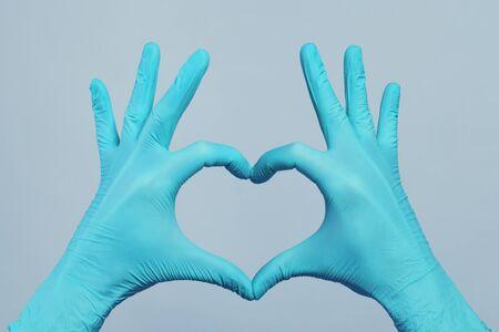 Hände in blauen Arzthandschuhen, die Herz auf grauem Hintergrund machen. Medizinisches Betreuungskonzept