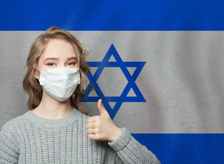 Happy woman in face mask holding thumb up on national flag Israel background. Flu epidemic and virus protection concept