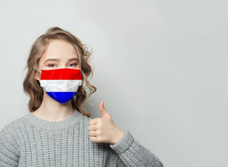 Happy woman in face mask holding thumb up with Netherlands flag background. Flu epidemic and virus protection concept Standard-Bild