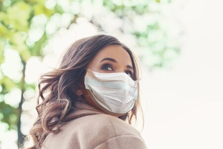 Stressed nervous woman in protective mask looking back outdoors