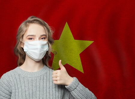 Happy woman in face mask holding thumb up on Vietnam  flag background. Flu epidemic and virus protection concept Stock Photo
