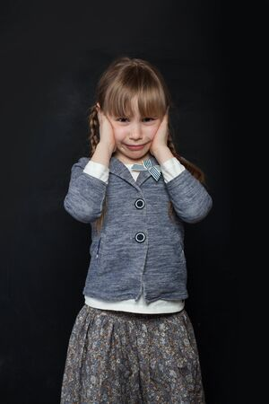 Sad child girl crying on black background Stock Photo