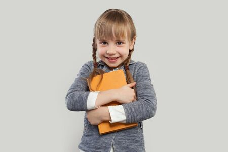 Child girl smiling and embracing book on white
