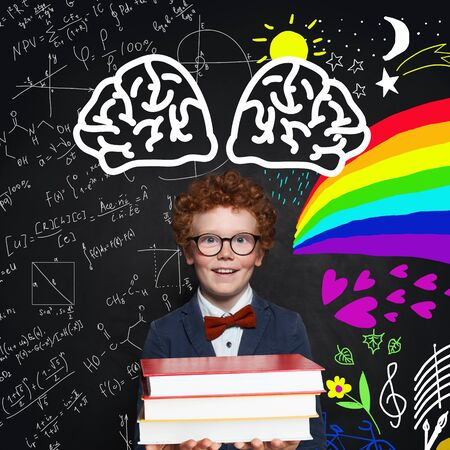Cute young boy holding books on school background