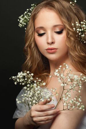 Portrait of young gentle woman with white flowers on black background Banque d'images