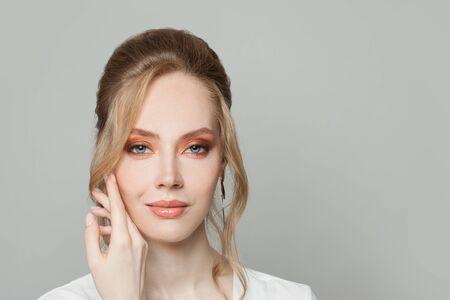 Jeune femme élégante avec une coiffure chignon sur fond blanc Banque d'images